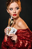 Attractive Girl In Red Shiny Dress Holding Joker And Queen Of Hearts Cards, Drinking Champagne Isola poster