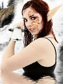 Live action role play character in costume in lake dressed as fantasy warrior elf.