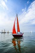 Yacht With Red Sails Sailing In The Sea Against The Background Of Other Yachts. poster