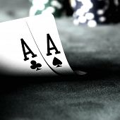 two aces on green table with blurry chips and background