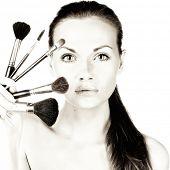 retrato de uma mulher bonita com pincéis para maquiagem
