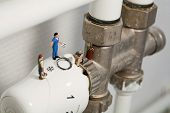 Miniature Plumbers Repairing A Thermostat