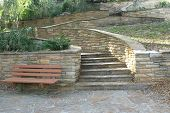 stock photo of fieldstone-wall  - Photo of a masonry staircase and retaining wall with a park bench 2 - JPG