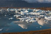 Scattered Melting Icebergs Near Jokulsarlon Glacier Lagoon Shore. Clouds Reflecting In The Water. Gl poster
