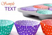 Colorful cupcake wrappers with baking pan on white background with copy space.  Macro with shallow d