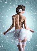 Young beautiful ballet dancer over Christmas background