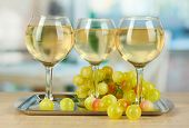 White wine in glass on salver on room background