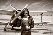 Beautiful girl in black jacket standing with aircraft behind. Retro black and white photo.
