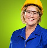 Portrait Of Happy Mature Woman Wearing Hardhat And Protective Eye Glasses On Green Background