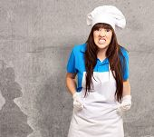 portrait of a female chef clenching, indoor