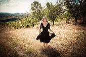 smiling young blond woman in elegant black dress running across field