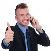 young business man talking on the phone while showing thumbs up with a smile on his face . on white