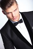 closeup cutout picture of an elegant young fashion man in tuxedo looking at the camera.on gray backg