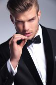 closeup of an elegant young fashion man in tuxedo looking at the camera while preparing to take a sm