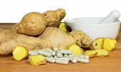 picture of naturopathy  - Fresh root ginger with whole and sliced rhizomes alongside a white ceramic pestle and mortar and a pile of capsules conceptual of plant extracts and supplements - JPG