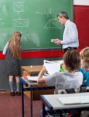 Rear view of little schoolgirl writing on board while teacher looking at her in classroom