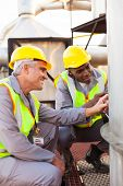 two petrochemical technicians inspecting fuel tank in plant