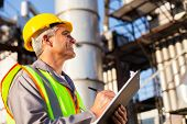 image of petroleum  - mid age petroleum factory worker working outdoors - JPG