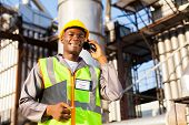 african oil and chemical worker talking on cell phone