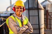 stock photo of ppe  - happy middle aged oil chemical industry worker inside plant - JPG