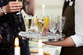 stock photo of trays  - Closeup of the hands of a waiter carrying a tray serving champagne and orange juice to guests at a catered function or wedding - JPG