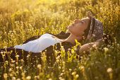 picture of beatitudes  - The girl in a hat dremet among wildflowers at sunset - JPG