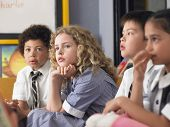 Thoughtful elementary students sitting in classroom