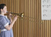 Side view of high school girl playing trombone in music class