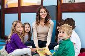 pic of daycare  - Portrait of young teacher and children with book sitting on floor in classroom - JPG