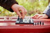 Grandmother hand makes move on chessboard in game in park outdoors, child hand lies on table in wait
