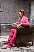 Profile portrait of young man in pink suit who sits motionlessly in old scuffed armchair and stares