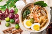 Singapore prawn noodles or prawn mee. Famous Singaporean food spicy fresh cooked har mee in clay pot with hot steam. Asian cuisine.