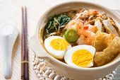 Singapore prawn mee or prawn noodles. Famous Singaporean food spicy fresh cooked har mee in clay pot