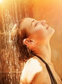 Attractive female taking shower with pleasure, cute girl with closed eyes enjoying warm water spray, luxury spa resort