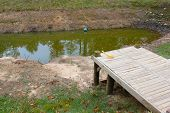 Wooden dock, too far away from the small almost dried out pond