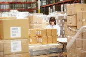 stock photo of dispatch  - Worker In Warehouse Preparing Goods For Dispatch - JPG