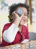 Portrait of cute little boy playing with alphabet block in classroom