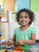 stock photo of classroom  - Portrait of smiling little girl assembling  puzzles in classroom - JPG