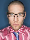 foto of male pattern baldness  - Portrait of a serious bald man in glasses against blue background - JPG