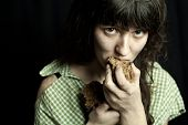 stock photo of beggar  - portrait of a poor beggar woman eating bread - JPG