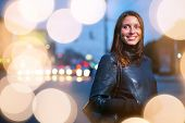 Portrait of a young woman in leather jacket in city street with illuminated bokeh circles background. Copyspace.