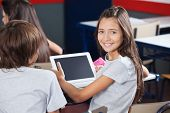 Portrait of little schoolgirl holding digital tablet at desk with classmates in classroom