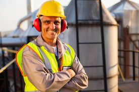 image of ppe  - happy middle aged oil chemical industry worker inside plant - JPG