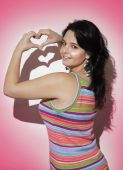 Girl forming heart shape with hands