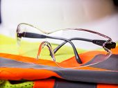 foto of personal safety  - Construction safety equipment with glasses in front of hardhat - JPG