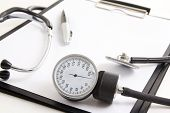 picture of sphygmomanometer  - close up of clipboard with blank paper sheet stethoscope and sphygmomanometer isolated on white background