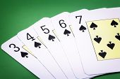 Spade straight flush on green background