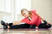 image of leg-split  - Smiling athletic woman stretches the muscles in a gym - JPG
