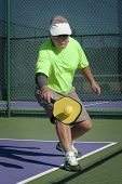 pic of pickleball  - Digital image of senior male pickleball player at edge of court hitting a backhand shot - JPG