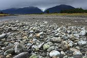 River from Fox glacier with rock foreground New Zealand